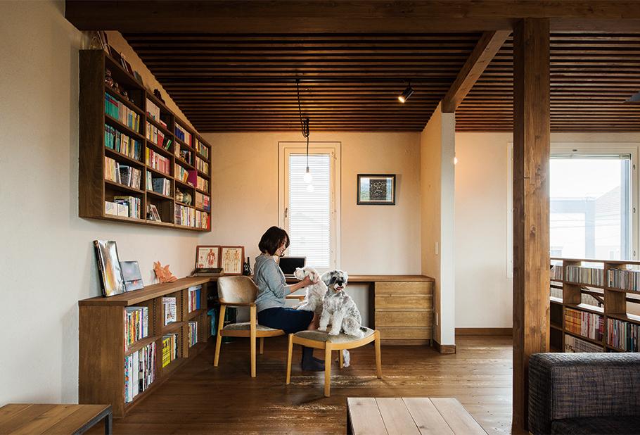 写真:リビングの一角に設けた書斎コーナー。蔵書の多いOさんの要望で、吹き抜けの手すり下や壁に本棚を造作