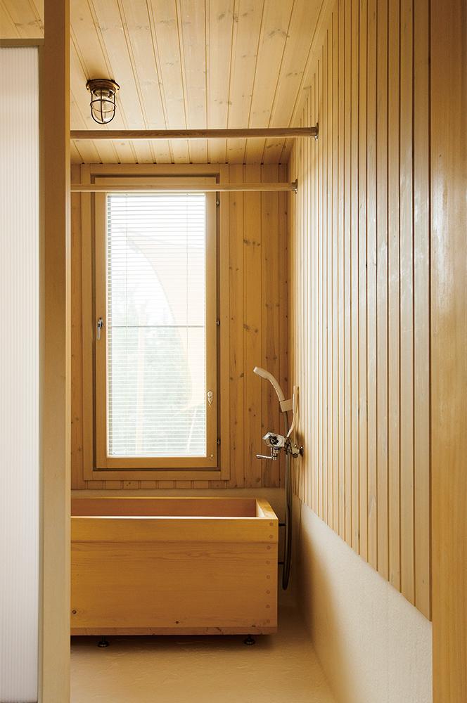 写真:コウヤマキを用いた浴槽とヒバ羽目板の壁、FRP仕上げの床を採用した1階浴室。洗剤の飛び散りを防ぐシャワーブースを手前に設けて、メンテナンスがしやすいように配慮