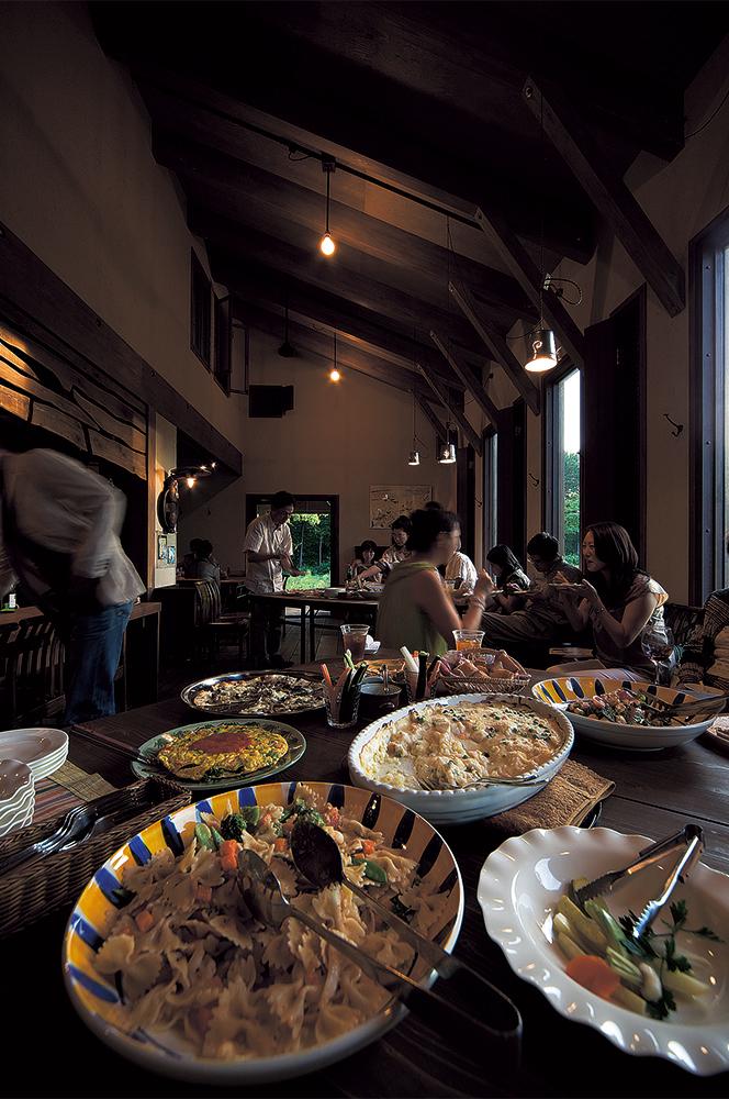 写真:屋根の傾斜をそのまま利用し梁を現しにした店内は、ヨーロッパの片田舎にあるレストランのような気さくな雰囲気