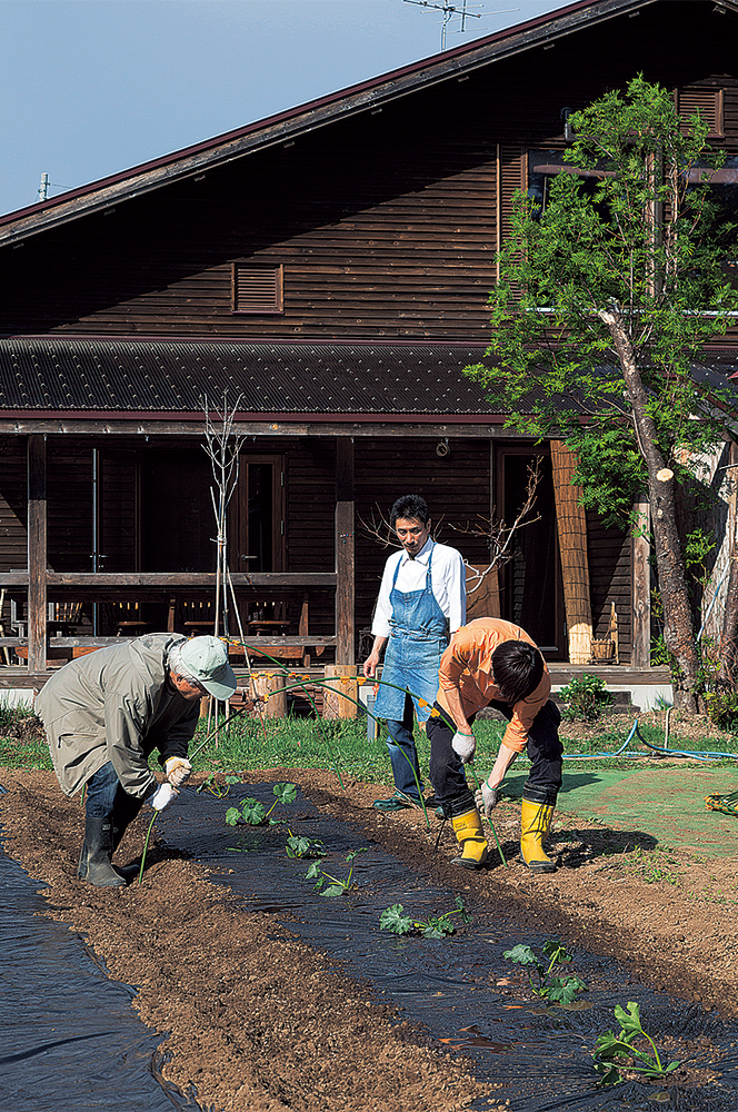 写真:畑仕事は農業に詳しい奥さんのお父さんが師匠。近所の農家の方たちが作業を手伝ってくれることも。ビニールハウスもあり、50種類以上の野菜を作る。夏から秋には近隣の子どもたちに野菜の収穫体験も行っている