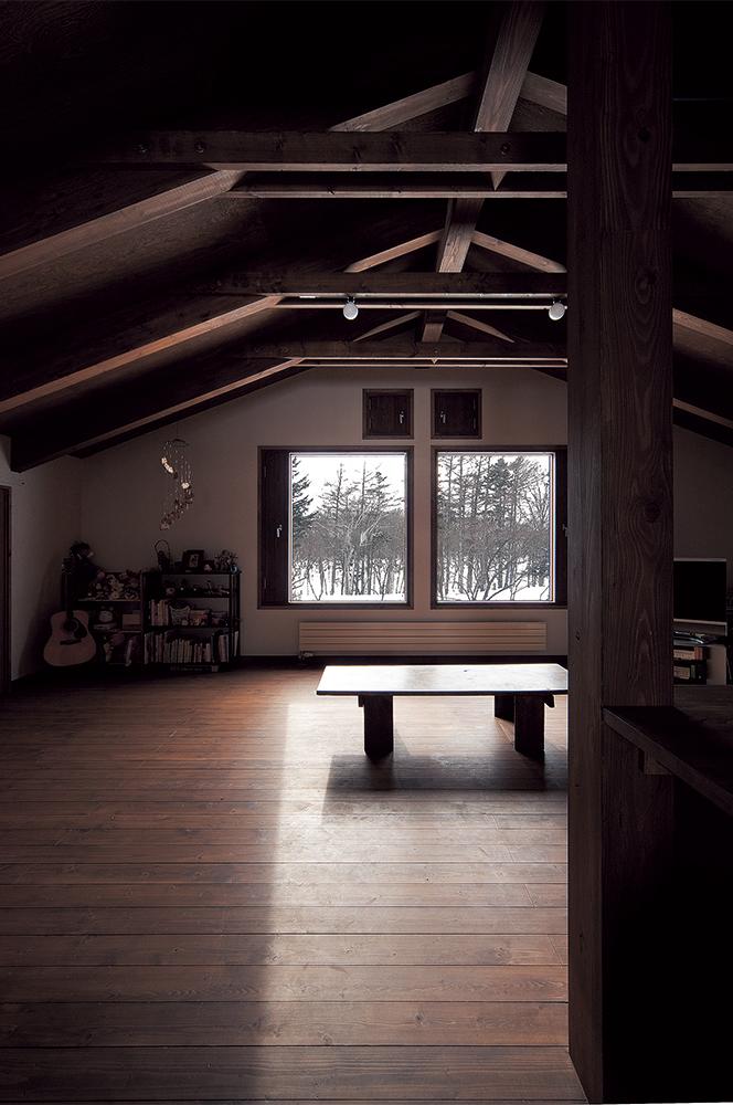 写真:住宅部分のリビングは仕切りを設けず大空間に。木の質感が存分に感じられる空間となっている。四季折々、外の景色を映し出すピクチャーウィンドウも、抜け感を演出しており効果的