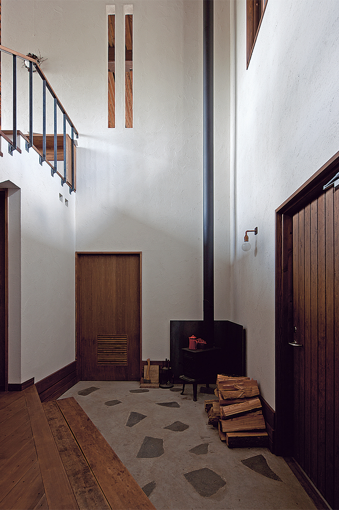 写真:玄関土間に置かれた小さな薪ストーブ。厳寒の美瑛にて、このストーブ一台だけで浴室以外のすべての空間を暖めた