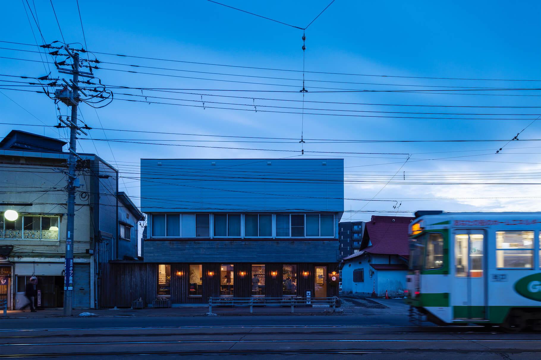 写真:路面電車の通りに面する湯川エンデバー。もともと海産物土産屋さんの一階を改装した