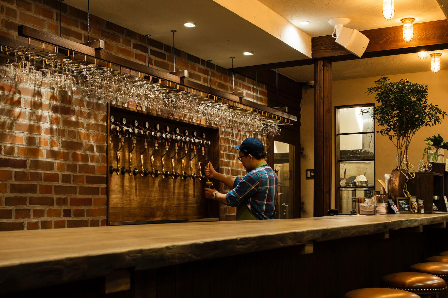 写真:10種類までクラフトビールが楽しめる。壁は野幌産のレンガを埋め込んだもの