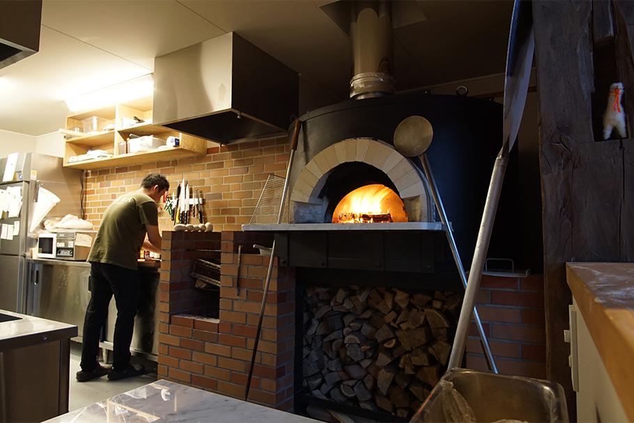 写真:石窯と厨房。レストランホールの目立つところに設置するため、厨房の換気ファンで煙の逆流がおきないように、加圧式の換気を計画