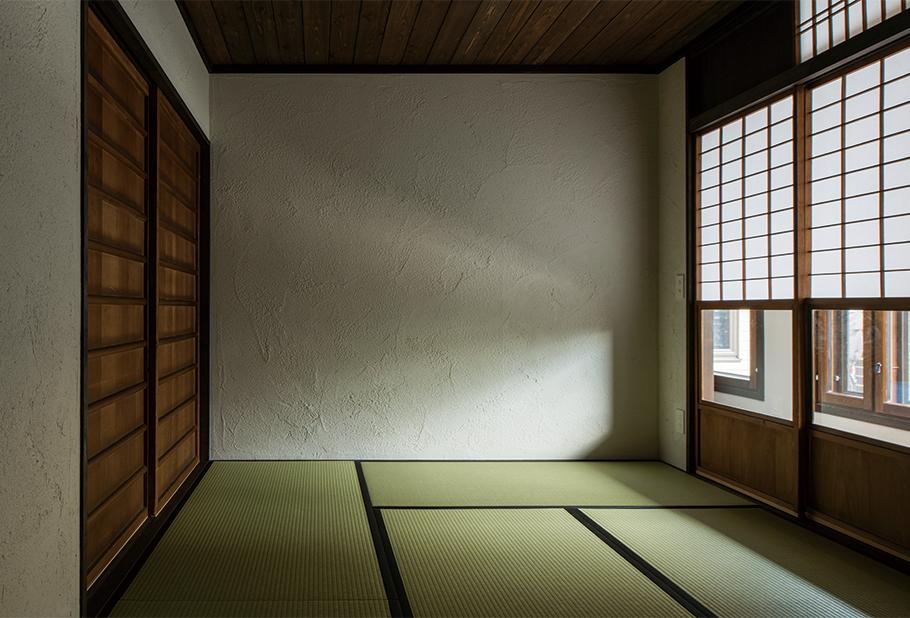 写真:共有のゲストルーム兼2世帯をつなぐ和室。あえて天井を低くし、畳に座ったときに落ち着く空間に。照明は天井にはなし。壁のコンセントから電源を取り間接照明を入れる予定。建具は以前の家のものを再利用した