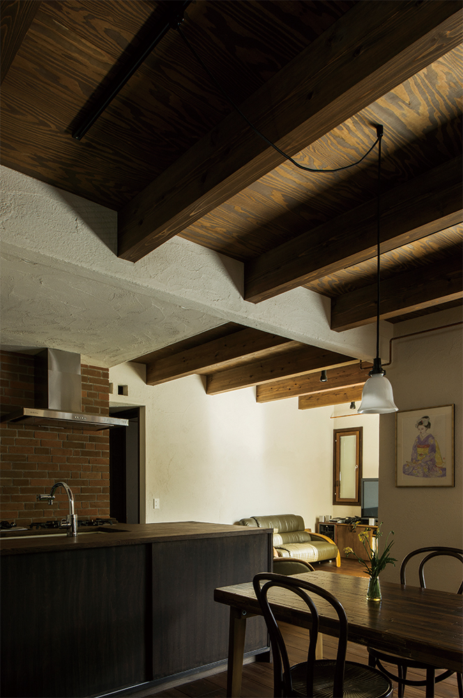 写真:重厚な印象に仕上げた1階の親世帯。天井を構造現しにしている点でも2階とずいぶんと印象が異なる。食器や家電は造作の棚にすべて収納されすっきり