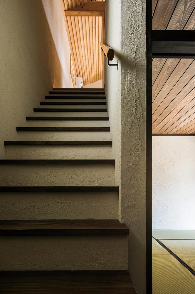 写真:子世帯へ続く階段と2世帯をつなぐ和室。印象の異なる2つの空間をこの階段が違和感なくつなぐ