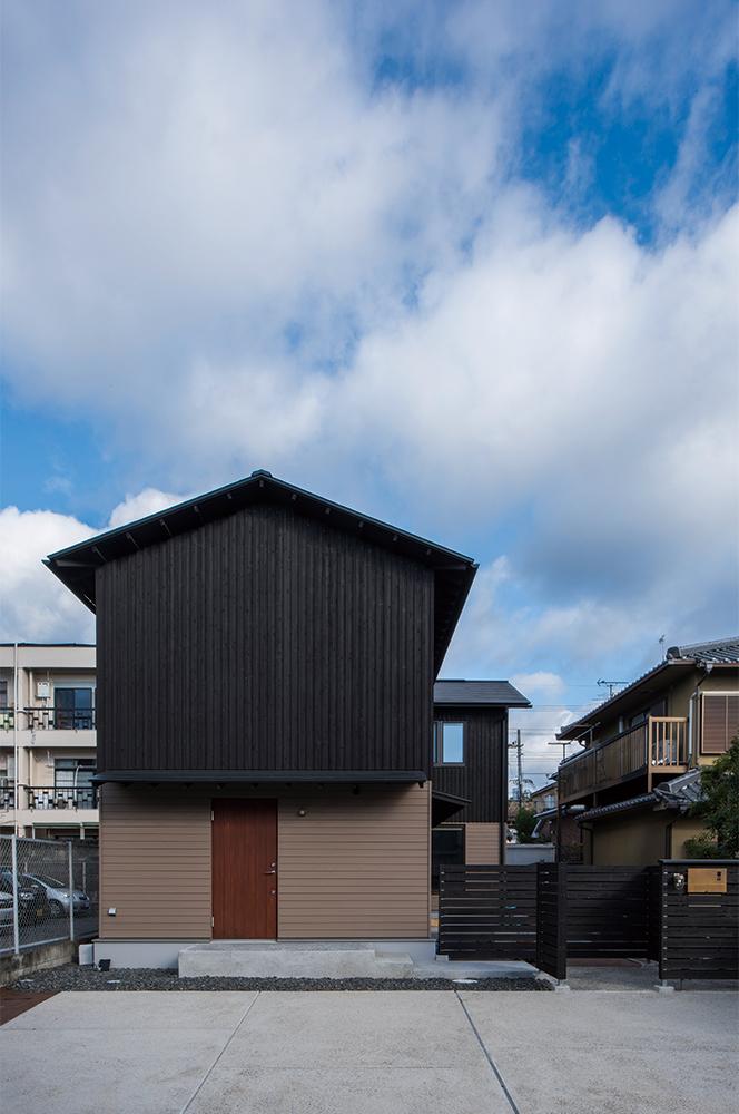 写真:スギ板の外壁は、地域の景観に関する条例に配慮しつつ2色使いに。正面が子世帯の玄関、右手の庭側に親世帯の玄関がある。今後庭には、ユズや北海道では育てづらいイチジクなどを植える予定