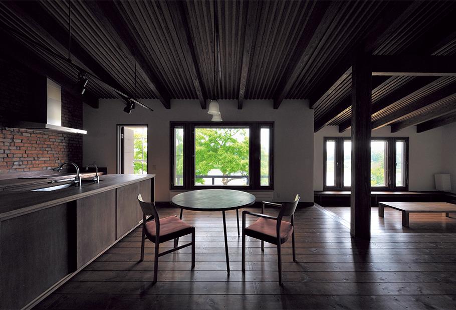 写真:オープンカウンターのキッチンとダイニング。右奥にあるリビングの床面を1段低くしただけで、空間にメリハリが生まれている