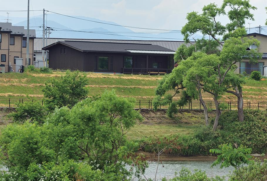 写真:川の対岸から望むと、Sさん宅は川面よりかなり高いところに位置しているのがわかる。平屋にはこういった自然条件を意識した設計も重要になる