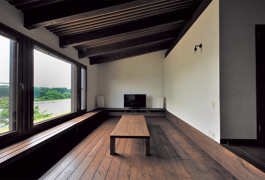 写真:リビングはSさん宅の特等席。ダイニングよりも川方向に張り出しており、座卓を置いて床に寝そべって風景を眺められるようになっている