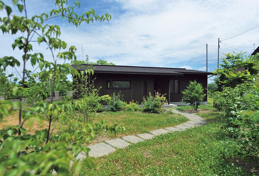 写真:長方形の敷地の再奥に建物を配置。道路からのアプローチに植えられた木は成長に従って森の様相を成すだろう