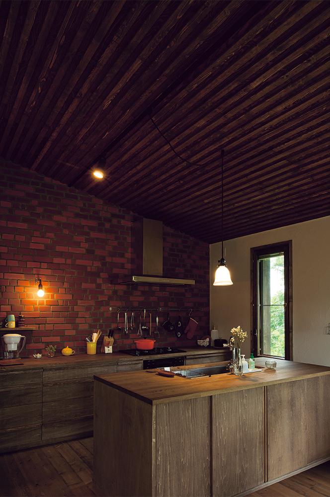 写真:木、レンガ、石こうの塗り壁など、月日とともに緩やかに味わいが深まる自然の素材を用いた室内。キッチンも既製品ではなく、製作とすることでコストも抑えられている