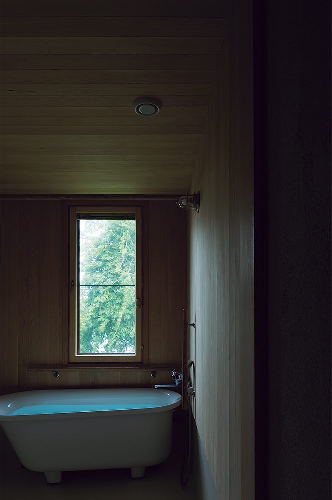 写真:木々が繁る傾斜地に向かって開口を設けた浴室。天井と壁の仕上げにヒバ材を使用している