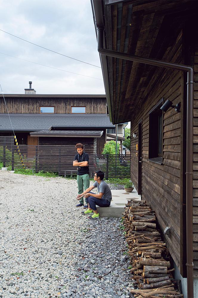 写真:Mさんと談笑する設計者の高田さん。奥に見える家が、この土地をMさん夫妻に紹介した方のお住まい。設計事務所が同じ2棟は、外装に道産のマツ材を使い、緑豊かなエリアにしっくりと溶け込んでいる