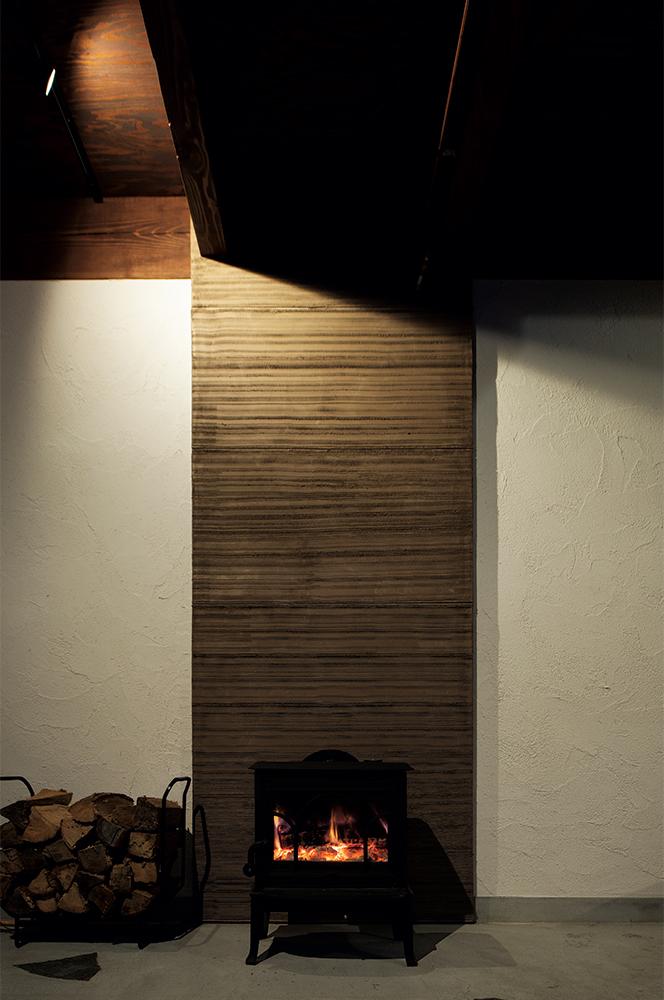 写真:大規模停電や災害に直面した時にも、電気に頼らずライフラインを確保できることも、安心の備えとしてこだわった。雪国に欠かせない暖房には温水パネルヒーターに加え、薪ストーブを採用。全室をストーブ一台で暖められるように、設計面も工夫が凝らされている。薪火で煮炊きもでき、災害時にも自立した暮らしを保つことができる