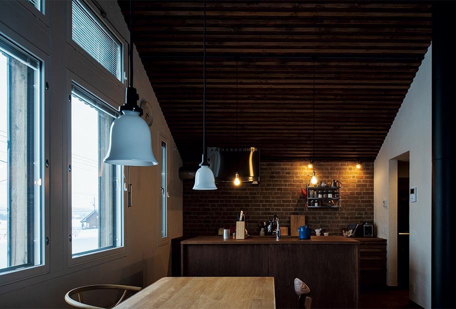"""写真:タモ無垢天板とレンガ壁で構成された造作キッチン。自然素材はデリケートと思われがちだが、Yさんは「はねた水や油も""""なかったこと""""にしてくれるおおらかさと頼もしさがある」と語る"""