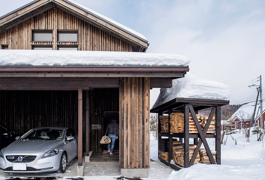 写真:トドマツ板張りの三角屋根の建物は、東川町が定める景観規約に基づいてデザインされた。冬の除雪が最低限で済むよう、屋根付きのアプローチとカーポートを設えた